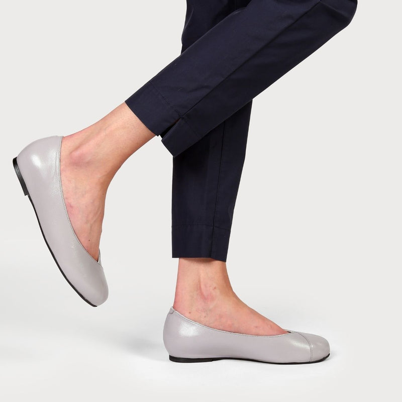 grey leather flats on legs in navy trousers