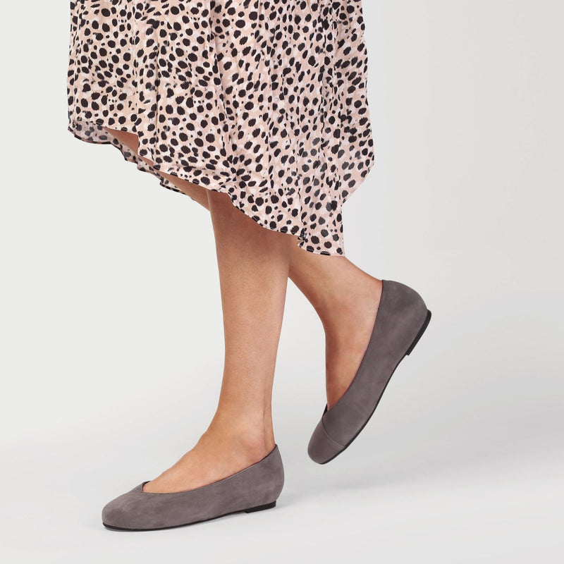 dark grey flat shoes worn by a woman in a dotty dress