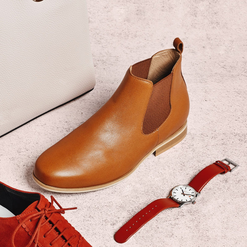 tan leather flat boot next to a red watch
