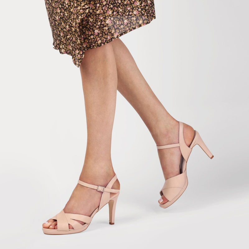 nude leather heeled sandals worn by a woman