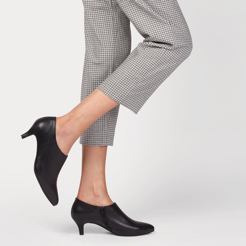 black shoe boots worn by a woman with crop trousers
