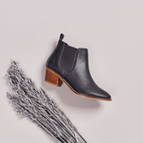 dark grey leather boots on grey background