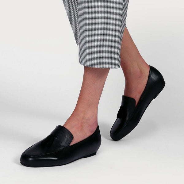 black leather loafers worn on feet