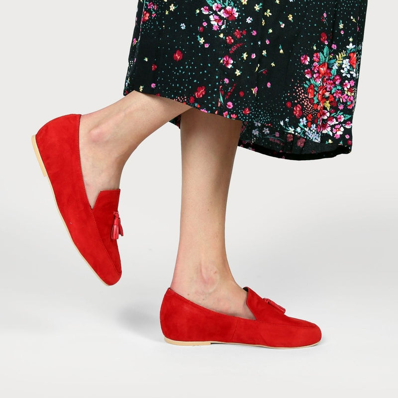 red suede loafers worn with a floral skirt