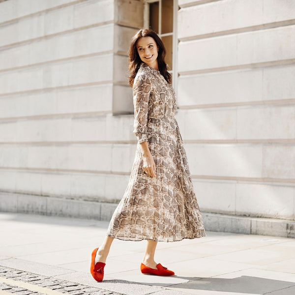 woman standing on street in snakeskin dress and red shoes