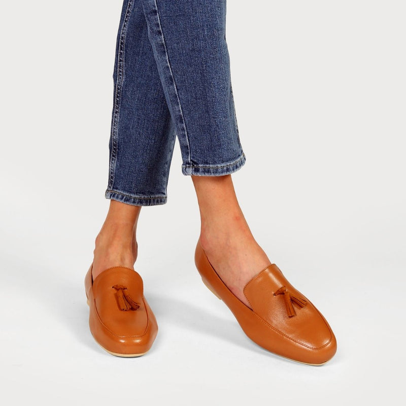 tan loafers worn on crossed legs in jeans