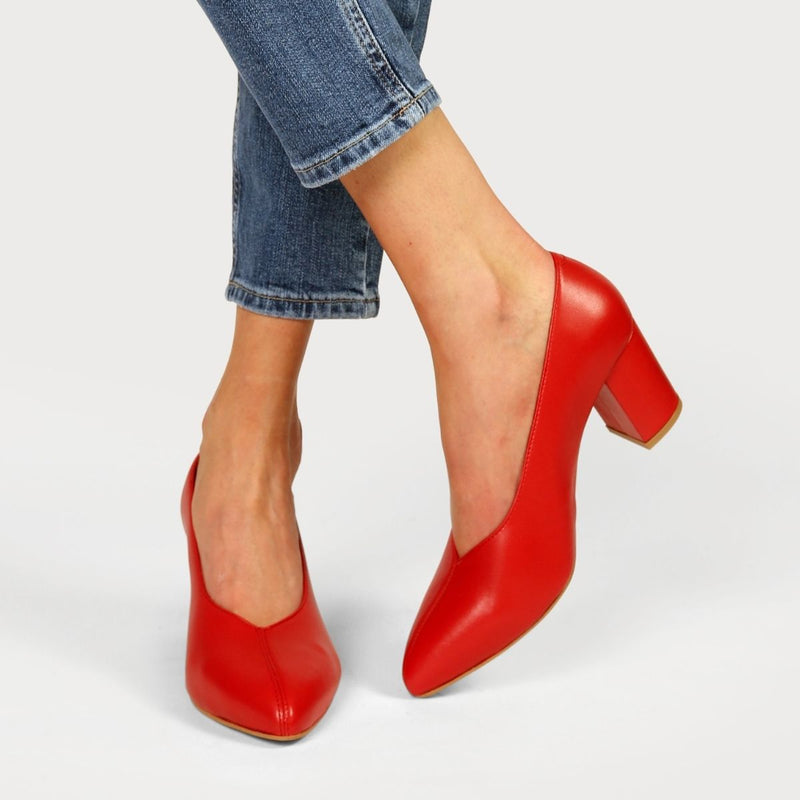 red heels worn on crossed legs in jeans