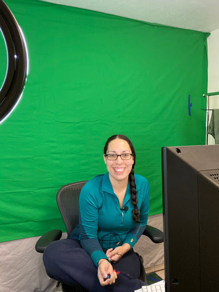 Alpine Parrot Founder and CEO, Raquel, smiling in front of a green screen.