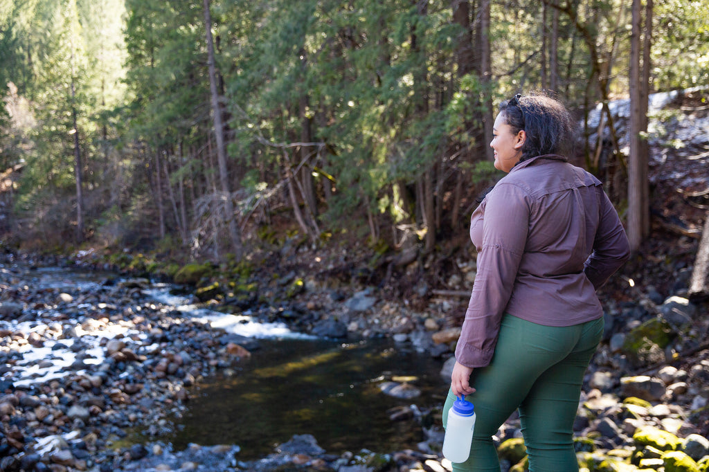 A woman stares at a beautiful river scene in her Ponderosa Pants.