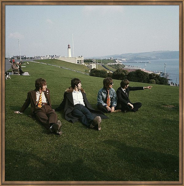 The Beatles pose for a group shot, sitting on the grass