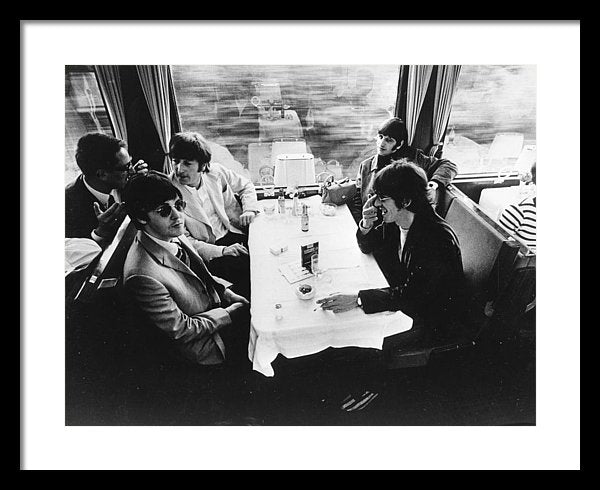 The Beatles relax in the buffet car of a train