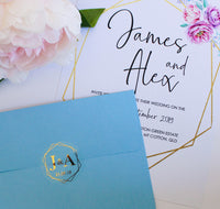 Beautiful geometric clear foil envelope seal on a blue envelope with wedding invitation with geometric border