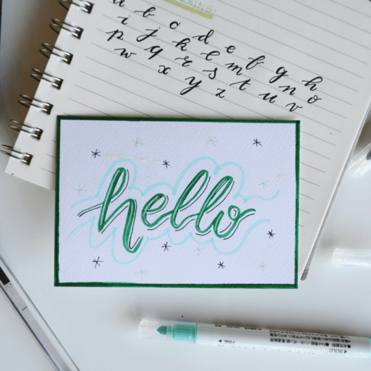 Image of word hello written out on card with notebook behind with alphabet