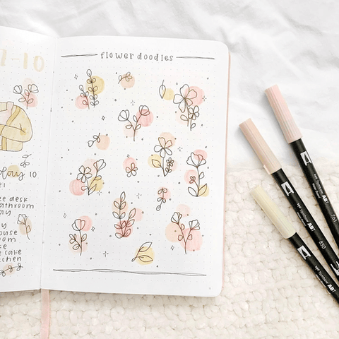 Open journal on fabric showing flower doodles