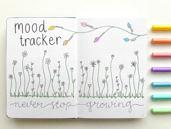 floral mood tracker in an open dot grid journal with pastel pens