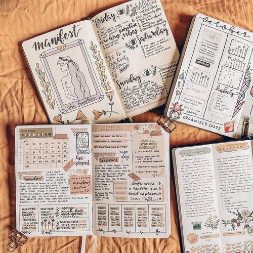 4 journals open on orange fabric with various doodles and text inside