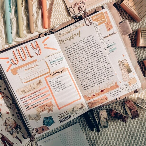 journal showing July page open on fabric with pens