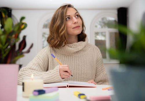 Woman thinking with pen in hand and bullet journal on table with candle in front