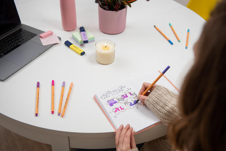 lady drawing in bullet journal on table