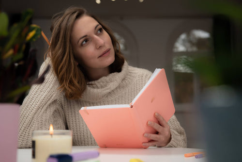 Woman with notebook and candle thinking