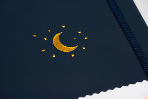 Close-up of vegan leather cover with gold debossed moon and star logo