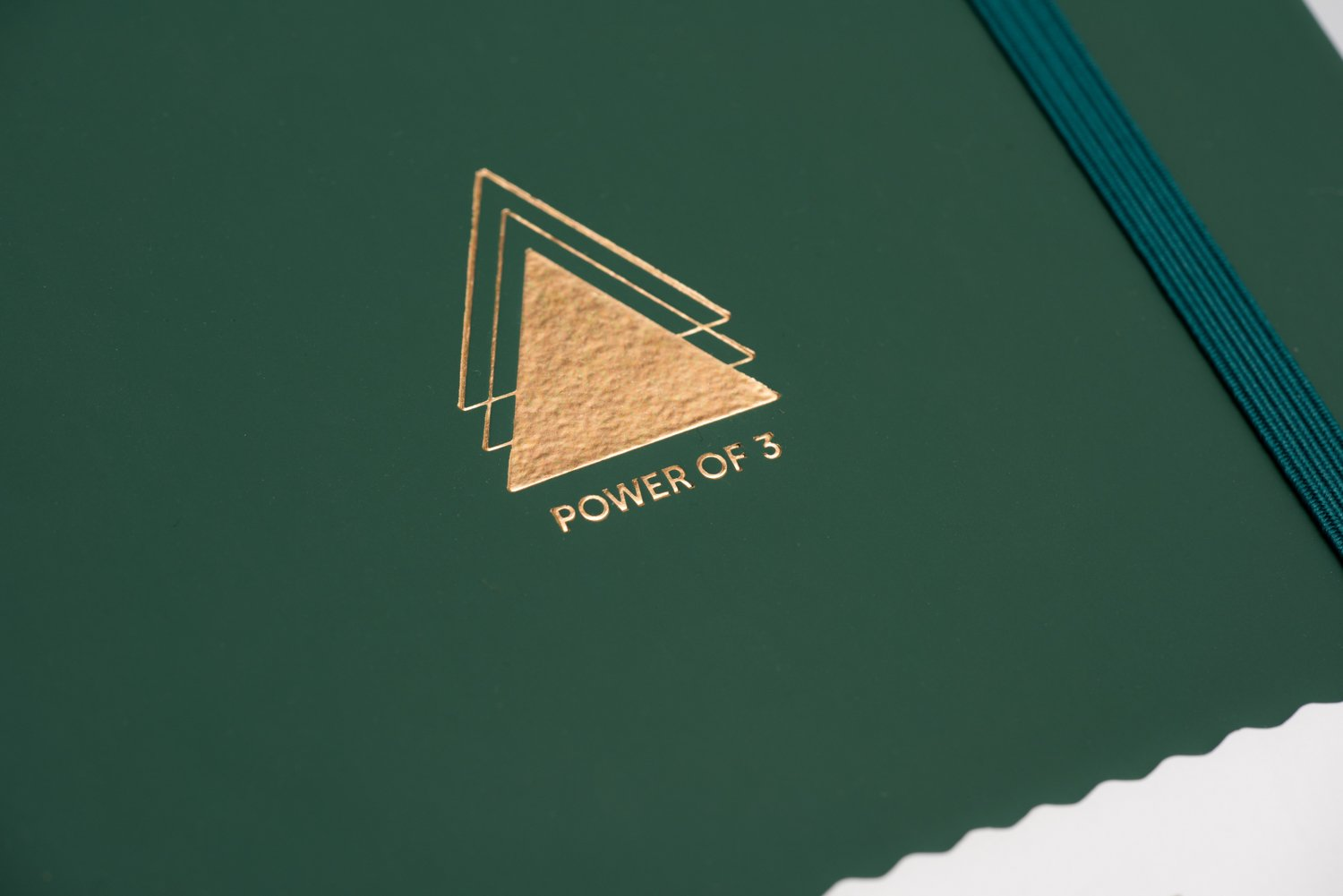 Close up of gold debossed power of 3 triangle emblem on green goal planner