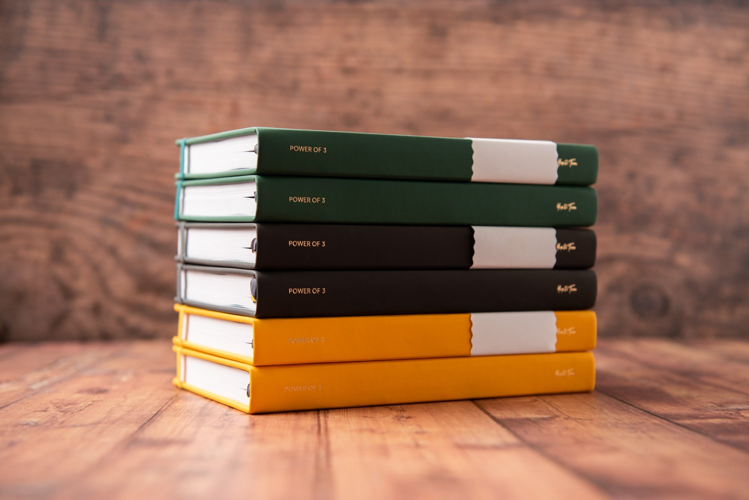 Stack of 6 goal planners in yellow, charcoal and forest green on wooden desk.