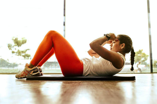 Woman doing sit up on wooden floor