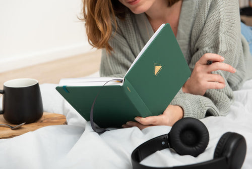 Woman lying down looking in undated goal planner with mug and headphones
