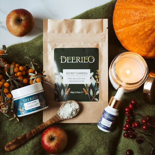Deerieo Discovery and Travel Set of face cream, facial oil serum and exfoliating facial mask on a green cashmere jumper surrounded by red apples, soy candles and orange pumpkin in Autumnal decoration.
