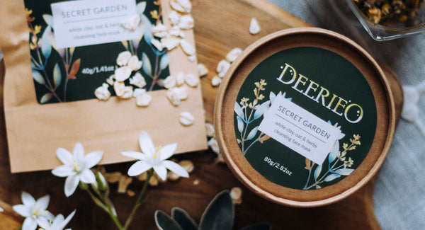 Deerieo Secret Garden natural exfoliating face mask on wooden board with white flowers.
