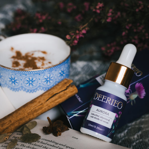 Deerieo Aurora rejuvenating oil serum with bakuchiol, vitamin C and coenzyme Q10 on a grey blanket with open book, cinnamon, spiced latte and purple heather.