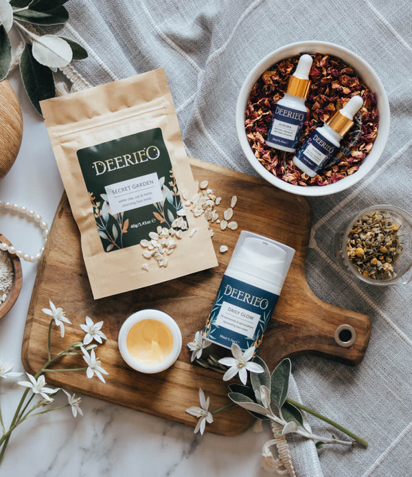 Deerieo natural skin care face moisturizer, clay face mask, oil serum on grey linen, white marble and olive wood chopping board with herbs, white flowers and pearl necklace.