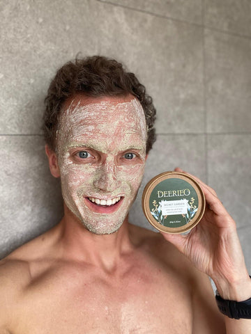 A smiling man with exfoliating face mask on holding Deerieo Secret Garden natural face mask tub.