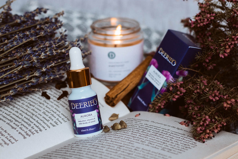 Deerieo Natural Skincare Aurora oil face serum and natural soy candle on a open book with lavender and spices