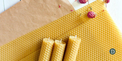 beeswax candles on a brown paper and white wood background