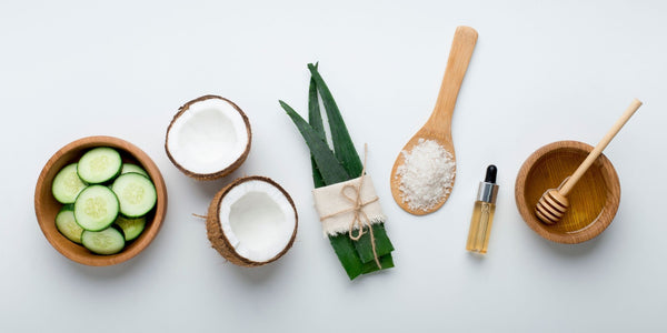 natural skin care ingredients like coconut, aloe vera and honey in a flat lay display.