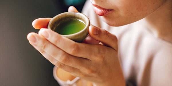 Woman drinking green tea from a small ceramic cup.