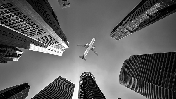 black and white plane flying over city