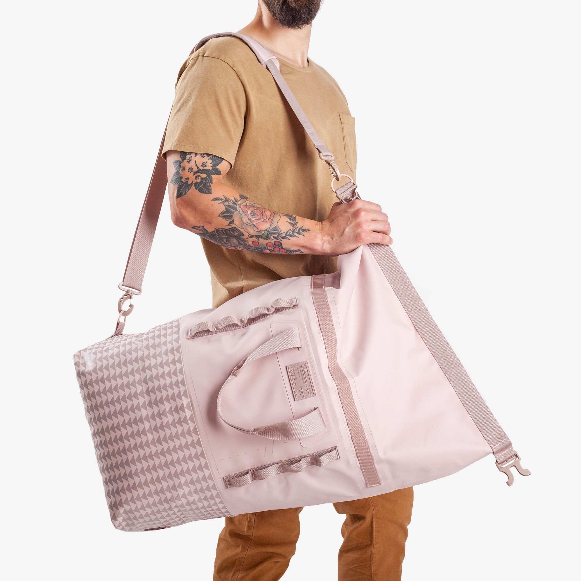 Model carrying So iLL Jason Mamoa Dirt Bag 45L in Pink over the shoulder