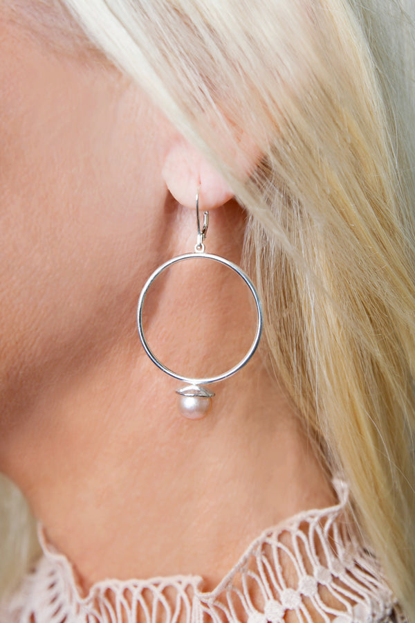 Profile view of a model's head with a Pareure Grit Series Sterling Silver Drop Hoop Earring with a white pearl in her ear