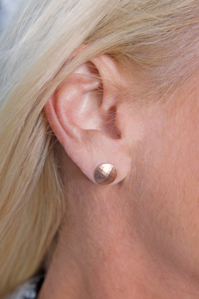 Image of a models ear with a Pareure 360º Series 18K Rose Gold Vermeil Small Button Stud Earring inserted into it