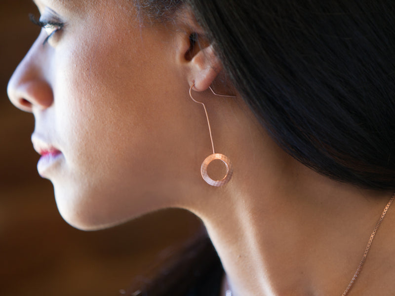 Profile view of model face and neck with a Pareure 360º Series 18k Rose Gold Vermeil Small Kinetic Earring inserted in her ear