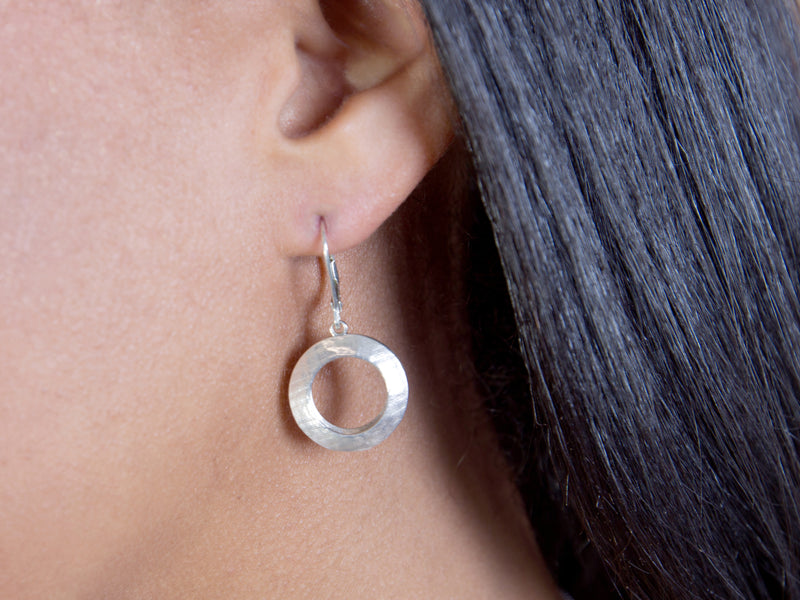 Model's ear with a Pareure 360º Series Sterling Silver Small Hoop Earring inserted in it