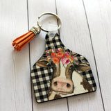 Cow Tag Key Chain with cow with flowers on buffalo plaid background with tassel