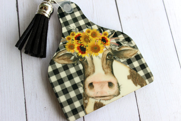 Cow Tag Key Chain with cow with sunflower crown on buffalo plaid background with tassel