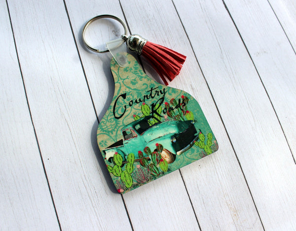 Country Roads Cow Tag shaped Key Chain with Turquoise Truck, Cactus, Tassel
