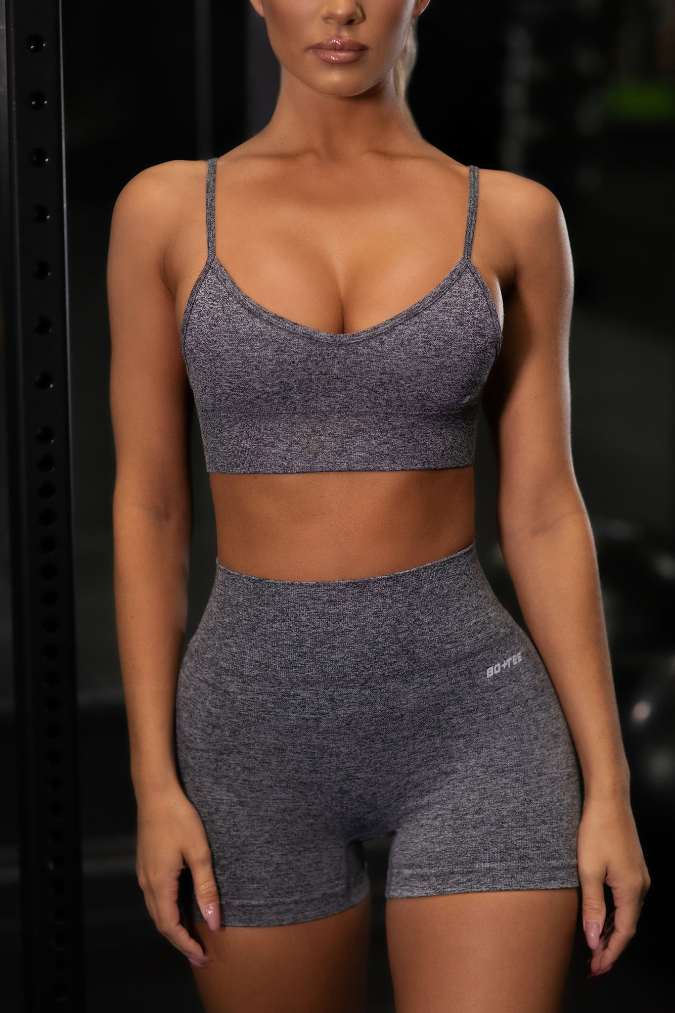 Plain black marl V neck sports bra with ribbed underband and thin adjustable straps. Image 1 of 6.