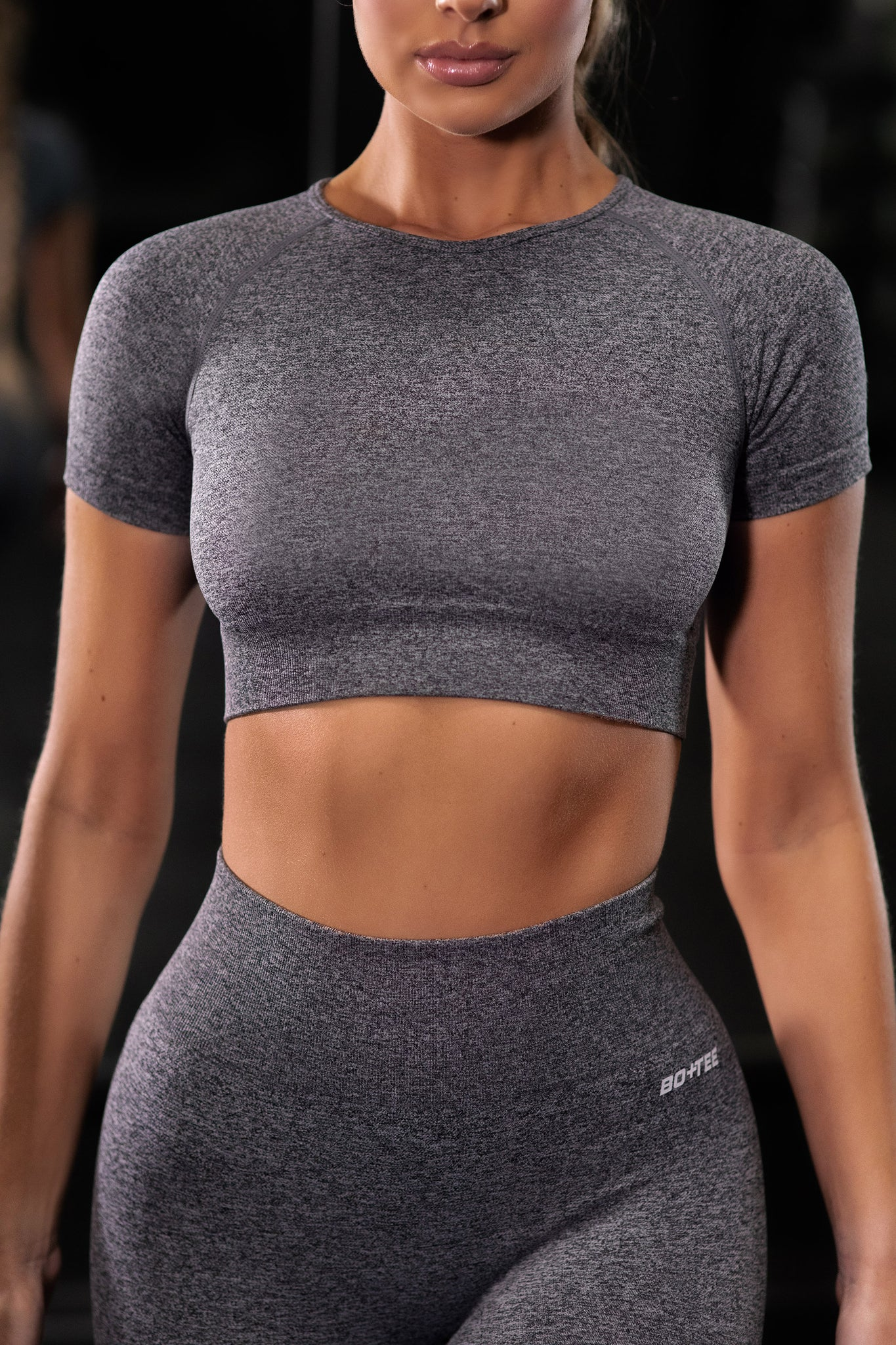 Plain black marl seamless short sleeve crop top with ribbed underband and round neck. Image 1 of 6.