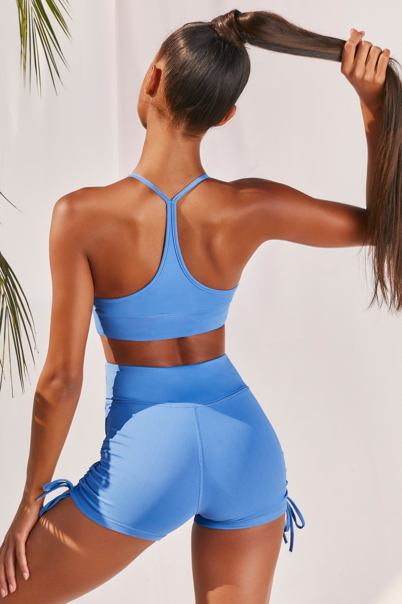 Plain bright blue slinky V neck sports bra with ruched centre and racer back. Image 3 of 6.